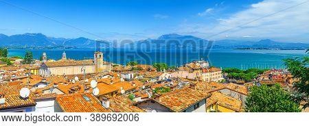 Panorama Of Desenzano Del Garda Town With Red Tiled Roof Buildings, Garda Lake Water, Monte Baldo Mo