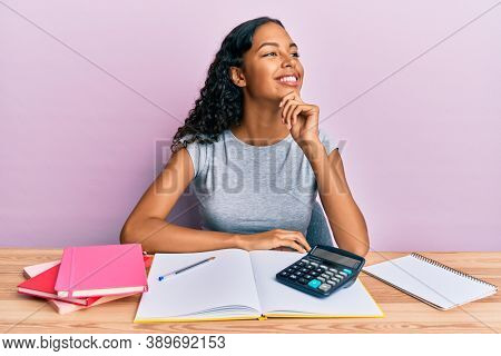 Young african american girl accountant working at the office with hand on chin thinking about question, pensive expression. smiling with thoughtful face. doubt concept.