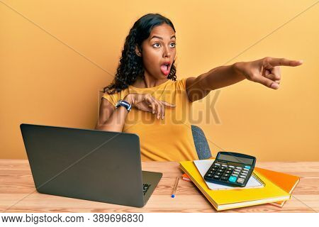 Young african american girl working at the office with laptop and calculator pointing with finger surprised ahead, open mouth amazed expression, something on the front