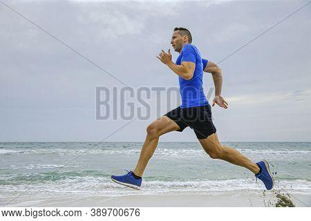 Man Athlete Middle-aged Runner Running On Sea Sandy Beach