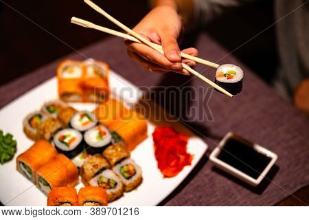 Person Eating Sushi With Chopsticks In Restaurant. Crop Anonymous Person With Chopsticks Eating Vari