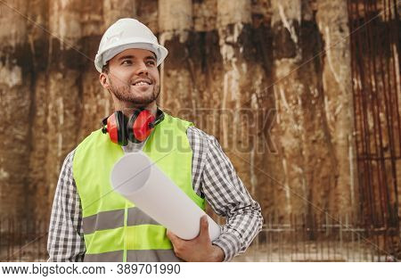 Positive Adult Male Builder In Workwear And Hardhat With Protective Headphones Holding Blueprint And