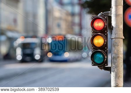 Blurred View Of City Traffic With Traffic Lights, In The Foreground A Semaphore With A Red And Yello