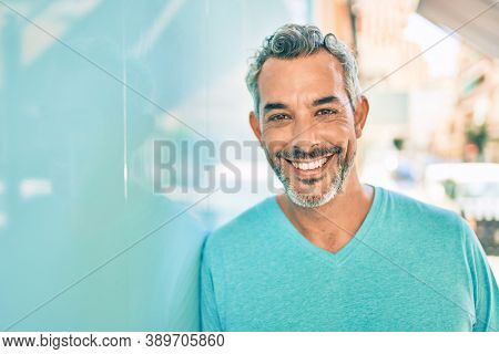 Middle age grey-haired man smiling happy leaning on the wall at street of city.