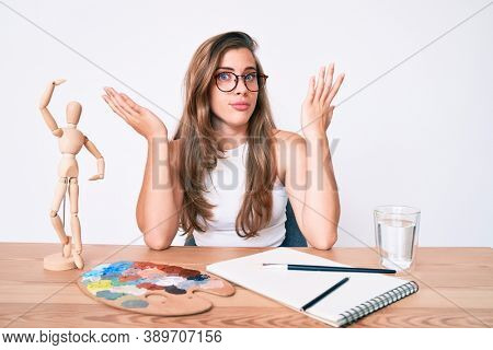 Beautiful young caucasian woman artist painter sitting on desk clueless and confused with open arms, no idea and doubtful face.