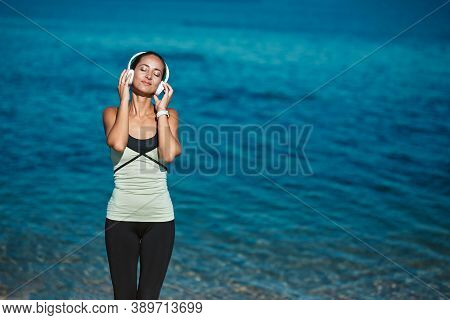 Woman Enjoying Music In Headset. Calm Sea And Fresh Air. Meditation Time And Contemplation Nature Co