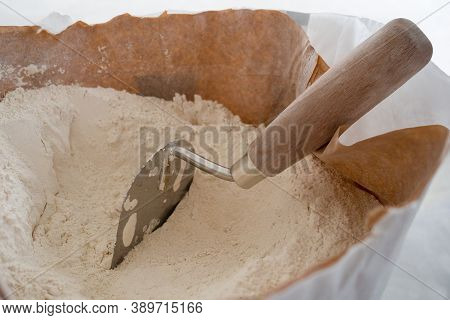 Close-up Of Plaster Trowel In Full Open Paper Bag Of Putty Powder For Wall Decoration,caulk Or Glaze