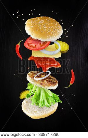 Burger Components Floating In The Air: Red Peppers, Cucumbers, Cheese, Ketchup, Onion, Cutlet, Tomat