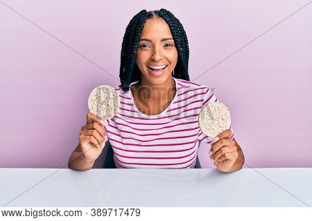 Beautiful hispanic woman eating healthy rice crackers smiling and laughing hard out loud because funny crazy joke.