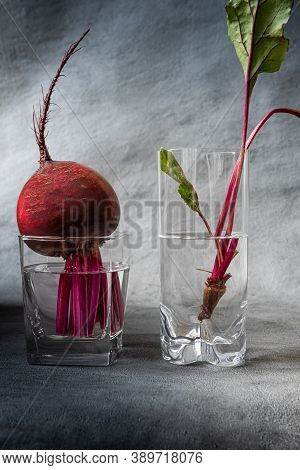 Close-up Of Fresh Bright Red Beetroot And Beetroot Leaves In Two Glasses Filled With Clean Water. Ve