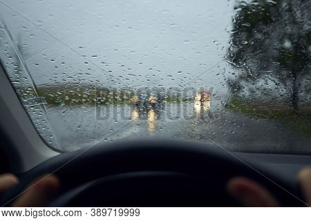 Driving In Heavy Rain. Raindrops On Windshield Of Car Against Traffic In Crossroad.