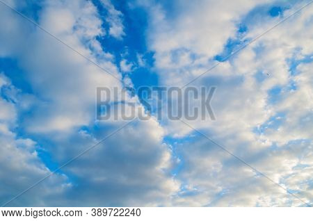Blue sky background, white dramatic fluffy sky clouds lit by sunset light. Sky landscape. Blue sky background, vast sky landscape, sky scene with dramatic clouds