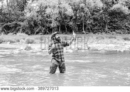 Fishing Masculine Hobby. Brutal Man Wear Rubber Boots Stand In River Water. Weekend Activity. Fisher
