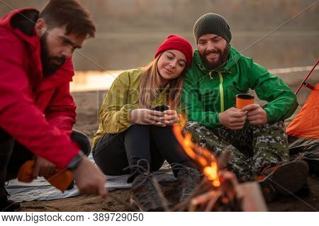 Young Man And Woman With Cups Of Hot Drink Watching Male Friend Making Fire While Resting On Campsit