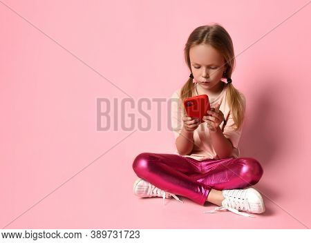 Blonde Little Girl In T-shirt, Leggings And Sneakers. She Smiling, Using Her Red Smartphone While Si