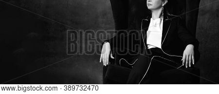 Black And White Cropped Photo Of A Woman In A Black Pantsuit Sitting In A High Chair In A Comfortabl