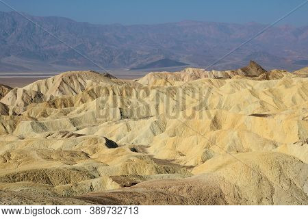 Arid Rolling Eroded Hills With Barren Mountains Beyond Taken On An Arid Plateau At Zabriskie Point I