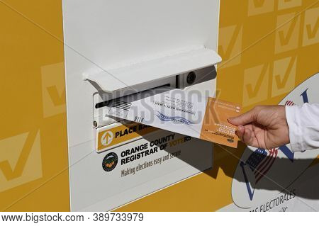 IRVINE, CALIFORNIA - 14 OCT 2020: Woman placing mail in ballot in an Official Ballot Drop Box in in Harvard Park, Irvine, Orange County, California.