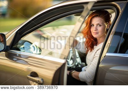 Pretty, young woman  driving a car  - Invitation to travel. Car rental or vacation.