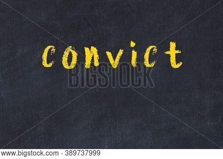 Chalk Handwritten Inscription Convict On Black Desk