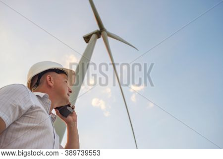 Windmill Engineer Talking On The Phone On Windmill And Sky Background.  A Man In A Helmet Supervises