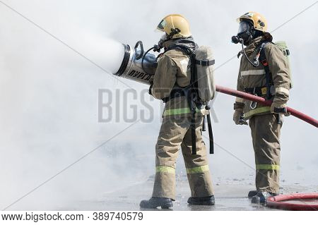 Two Firefighters Extinguish Fire From Fire Hose, Using Firefighting Water-foam Barrel With Air-mecha