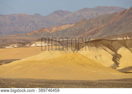 Eroded Barren Hills And Sand Dunes With Rural Mountains Beyond Taken On An Arid Plateau At The Mojav