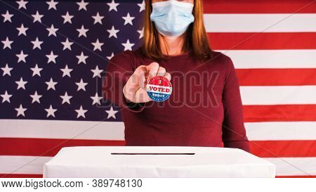 Voting Woman With Face Mask Showing I Voted Today Button At 2020 American Presidential Elections.