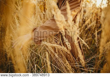 Stylish Boho Woman Holding Hand On Grass And Herbs In Autumn Field In Warm Sunset, Carefree Moment