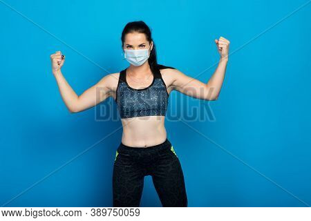 Young Strong Fitness Woman In A Face Mask Working Out Isolated On Blue Wall Background Studio.