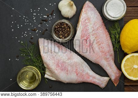 Seafood. Sea Perch On A Black Board. Red Sea Bass On A Black Board With The Ingredients For It Cooki