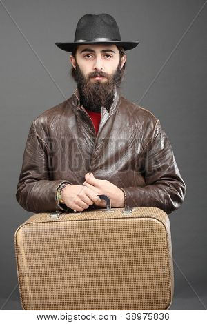 Traveler with suitcase, dressed in jacket and hat and beard.