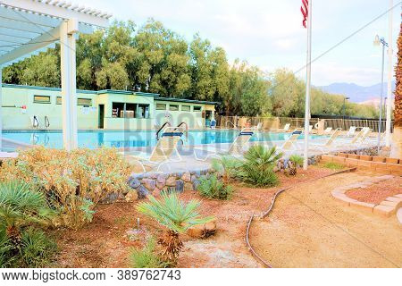 October 5, 2020 In Furnace Creek, Ca:  Poolside Chairs And Cacti Gardens Surrounding The Pool Taken