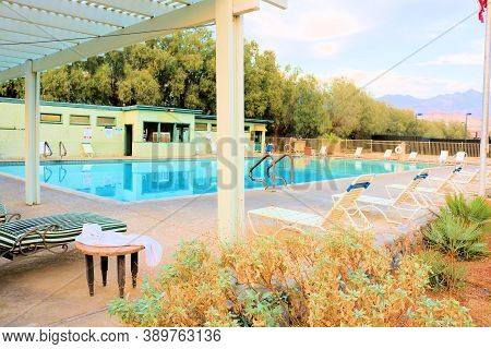 October 5, 2020 In Furnace Creek, Ca:  Poolside Chairs Besides Gardens And A Large Pool Besides A Ru