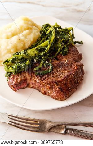 Fried Steak With Creamy Mashed Potatoes And Sauteed Broccoli Rabe