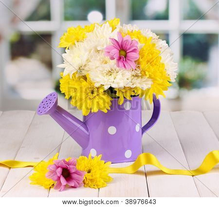 Purple watering can of peas with flowers on white wooden  table on window background