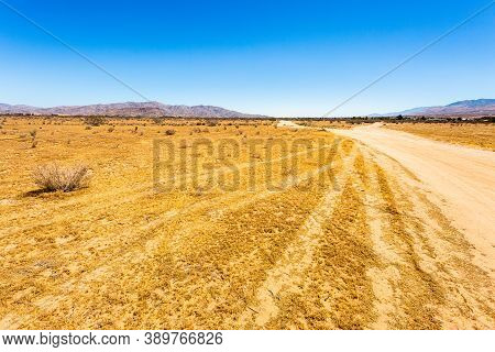 Summer Shot Of Desert View At Apple Valley, California Usa, With Mountains Over Clear Blue Sky And E