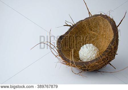 A Round Candy Covered With Coconut Shavings Lies In A Nut Shell. Half A Coconut. On White Background