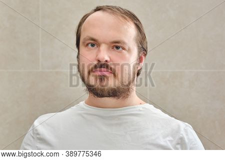 Face Of A Man With A Beard In A White T-shirt, Close-up. Portrait Of A Man 35-40 Years Old On A Beig