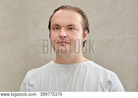 Face Of A Man In A White T-shirt, Close-up. Portrait Of A Man 35-40 Years Old On A Beige Background