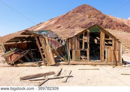 Collapsing Wooden Home Surrounded By An Arid Desert Plain And Barren Mountains Taken In The Historic