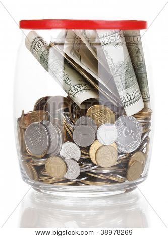 Clear glass jar for tips with money isolated on white