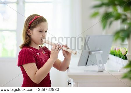 Child Playing Flute. Remote Learning From Home. Arts For Kid. Little Girl With Musical Instrument.