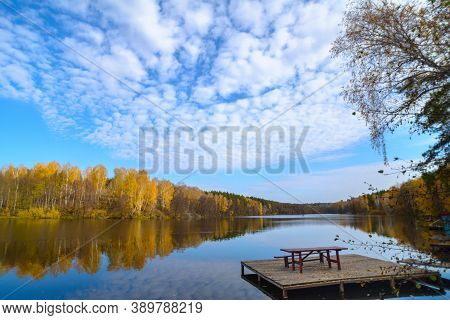 Beautiful Autumn Landscape With Clear Blue Lake And Yellow Autumn Trees. A Small Wooden Pier With A