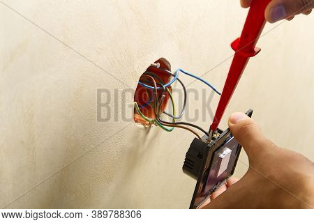 Electrician Installing Light Switch On Painted Wall With Screwdriver. Man Installing Light Switch Af