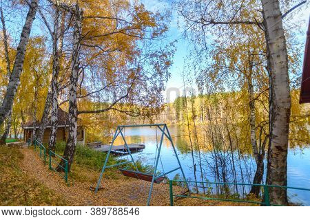The Swing Is Located In The Forest On The Lake Shore.