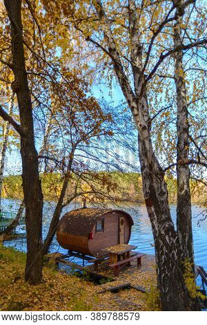 The Old Wooden House Is Located In A Yellow Autumn Forest On The Shore Of A Beautiful Blue Lake. A S
