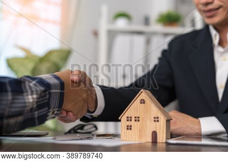 The Real Estate Agent Shakes Hands With The Client After Agreeing To A Contract For The Sale Of The