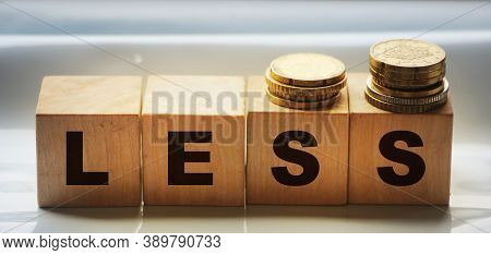 Less Word On Wooden Alphabet Blocks And Stack Of Coins. Less Spend, More Saving Business Concept