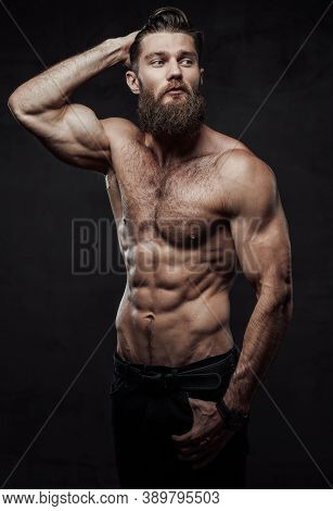 Brutal Bearded Guy With Naked Torso And Muscular Build With Hand In Pocket And Hand Under Head Posin